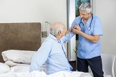 Male caretaker assisting senior man to get up from bed at nursing home