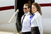 Confident airhostess and pilot looking away while standing against private jet