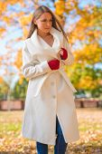 Attractive Serious Model in Elegant White Autumn Coat and Red Gloves Looking at Left Side Frame. Isolated on Nature Background.