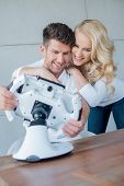 Happy Sweet Young Couple Having Fun with Cool Modern Gadget o Brown Table.