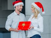 Beautiful woman giving her husband a Christmas gift in colorful red wrapping paper as they stand smi