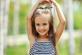 Portrait of Little caucasian girl, against green of summer park.