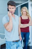 Handsome casual young man talking on his mobile watched by his wife standing with an angry expressio