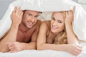 Attractive young couple lying on their stomachs on the bed peeking out from under the bedclothes with happy smiles