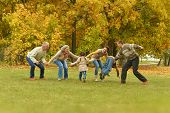 family relaxing in autumn forest