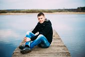 Young Handsome Man Sitting On Wooden Pier, Relaxing, Thinking. Casual Style - Jeans, Jacket