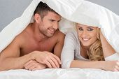 Close up Middle Age Romantic Couple on Bed with White Cover. Isolated on Gray Background.