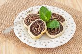 Brazilian Chocolate Dessert Bolo De Rolo (swiss Roll, Roll Cake) On White Plate With Mint