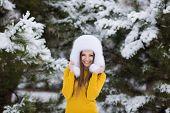 Portrait of a beautiful young woman in a winter park.