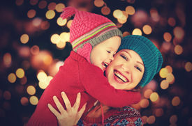 stock photo of mother baby nature  - happy family mother and baby little daughter playing in the winter for the Christmas holidays - JPG