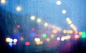 Drops Of Rain On Glass With Defocused Lights. Urban Abstract Background
