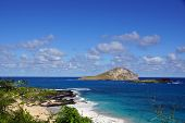 Makapuu Beach With People In The Water, And Rabbit And Rock Island In The Distance
