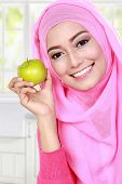 picture of muslimah  - cheerful young muslim woman holding an apple - JPG