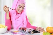 picture of muslimah  - portrait of young muslim woman enjoying a breakfast while reading a magazine - JPG