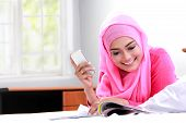 picture of muslimah  - portrait of young muslim woman reading a magazine on bed - JPG