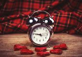 foto of analog clock  - Retro alarm clock with cookie on a table - JPG