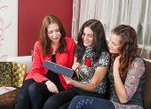 Three Young Women Friends Chatting At Home And Using Laptop To Look At New Photo Or Browsing Interne