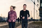 Active Young Couple Jogging In An Urban Street