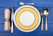 Plate With Silver Cutlery On An Old Blue Table