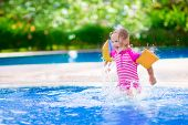 stock photo of swimming pool family  - Adorable little girl with curly hair wearing a colorful swimming suit playing with water splashes at beautiful pool in a tropical resort having fun during family summer vacation - JPG