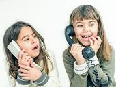 stock photo of 7-year-old  - Two seven year old girls talking on the old vintage phones with the white background - JPG