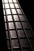 picture of fret  - Detail of the fret board of a bass guitar on a dark background.