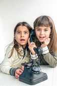pic of 7-year-old  - Seven year old girl talking on the old vintage phone and her sister eavesdropping her conversation - JPG
