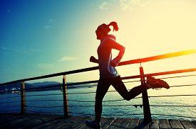 image of japanese woman  - healthy lifestyle sports woman running on wooden boardwalk sunrise seaside - JPG