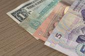 image of dirham  - Chinese Renminbi Euro UAE Dirham and US Dollar Banknotes on wooden table  - JPG