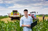 picture of combine  - Young attractive farmer with laptop standing in corn field tractor and combine harvester working in wheat field in background - JPG