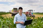 stock photo of combine  - Young attractive farmer with laptop standing in corn field tractor and combine harvester working in wheat field in background - JPG