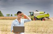 foto of harvest  - Young attractive farmer holding laptop in the field during rapeseed harvest - JPG