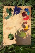 picture of paint palette  - Background with a wood palette with oil paint lying on the grass - JPG