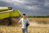 picture of farmer  - Young attractive farmer carrying laptop in the field during rapeseed harvest - JPG