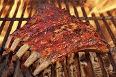 stock photo of baby back ribs  - Tasty Smoked Pork Spare Ribs On The Hot Flaming Barbecue Charcoal Grill - JPG