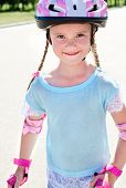 foto of roller-skating  - Cute smiling little girl in pink roller skates and protective gear outdoor - JPG