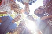 image of huddle  - Happy friends huddling in circle in the park on a sunny day - JPG
