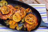 foto of thighs  - Delicious baked chicken thighs with lemon slices onion and zucchini served in cast - JPG