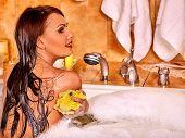 picture of bath sponge  - Young woman using bath sponge in bathtub - JPG