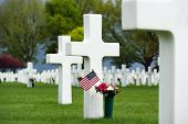 foto of headstones  - Flowers and a small flag of the US between cross headstones at the American military cemetery in the Netherlands - JPG