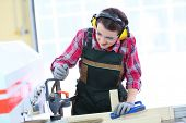 foto of sawing  - Young carpenter using electric sawing machine - JPG