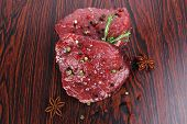 pic of peppercorns  - fresh raw beef fillet mignon on old retro style wood as background with rosemary peppercorn and salt - JPG