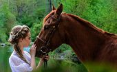 image of horse face  - Woman standing with horse near lake and touching horse face with her forehead - JPG