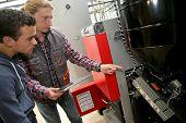 image of temperature  - Young man in professional training measuring heat pump temperature - JPG