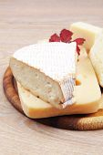 picture of cheese platter  - edam parmesan and brie cheese on wooden platter over wooden table - JPG