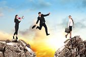 stock photo of gap  - Image of young businessman jumping over gap at the sunset - JPG