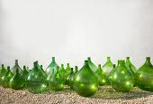 picture of olive shaped  - old green bottles of wine olive oil on white wall - JPG