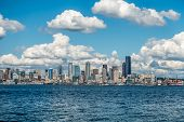 stock photo of puffy  - White puffy clouds hover over the Seattle skyline on a sunny day - JPG