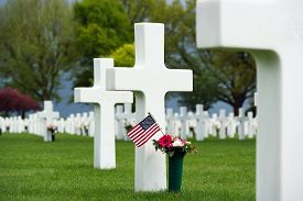 pic of headstones  - Flowers and a small flag of the US between cross headstones at the American military cemetery in the Netherlands - JPG