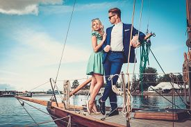 stock photo of sailing vessels  - Stylish wealthy couple on a luxury yacht  - JPG